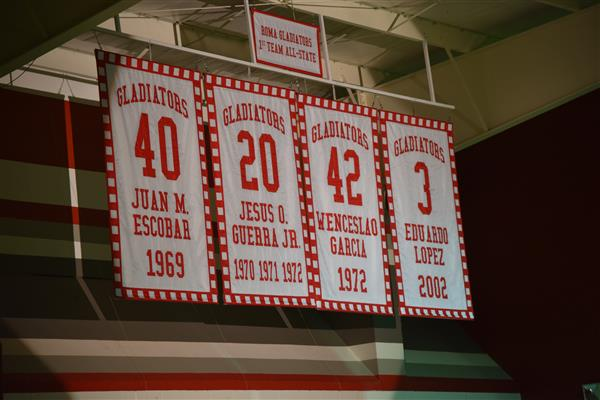 Retired jersey numbers hanging in the Roma High Gym.