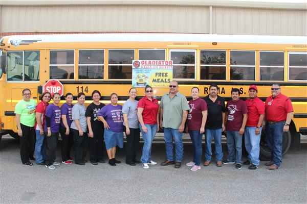 Bus drivers and cafeteria workers pose with a bus for a picture.